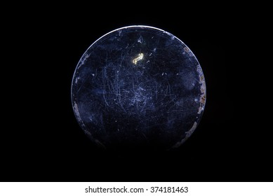 Old scratched magnifying glass on black background