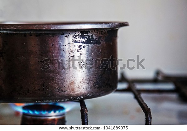 Old scratched metal cooker placed on a burning gas stove