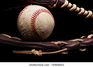 Old scuffed baseball sitting inside a brown leather glove.