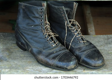 old scuffed black leather lace-up boots. The image is defocused.