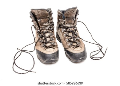 Old scuffed hiking boots isolated with laces on white background