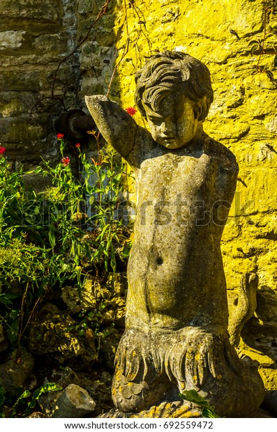 Old sculpture on the pedestal, beautifully preserved old artistic figure, decorative elements on the outside, vintage, boy
