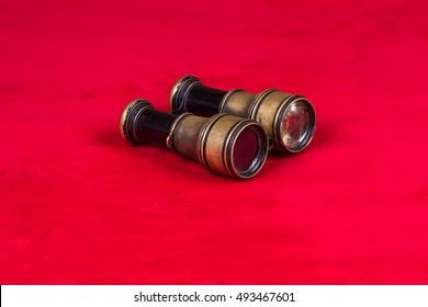 old sea binoculars on red velvet, old opera glasses