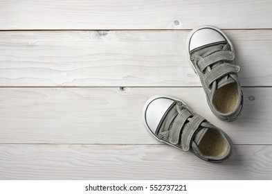 old secondhand black canvas shoes or sneakers for kids or baby foot on vintage white wood floor or table top view with copyspace