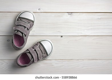 old secondhand pink with black canvas shoes or sneakers for kids or baby foot on vintage white wood floor or table top view with copyspace