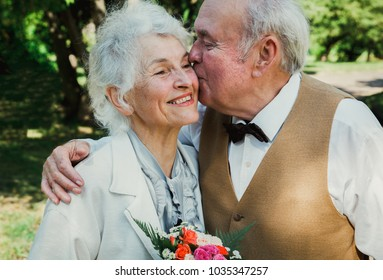 Old senior couple is walking in the green park. Grandmother and grandfather golden wedding anniversary celebration. Fifty years together love story of elderly people. Grandma and grandpa kissing.