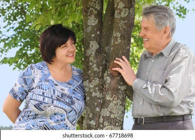 old senior and his adult daughter standing near tree and smiling, sunny summer