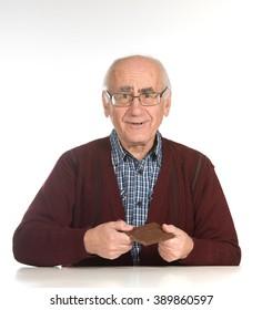 old senior man eating chocolate