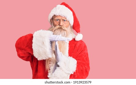 Old senior man with grey hair and long beard wearing traditional santa claus costume doing time out gesture with hands, frustrated and serious face