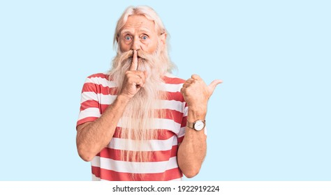 Old senior man with grey hair and long beard wearing striped tshirt asking to be quiet with finger on lips pointing with hand to the side. silence and secret concept.