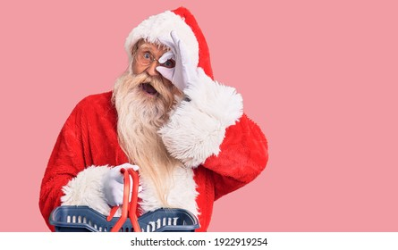 Old senior man with grey hair and long beard wearing santa claus costume holding shopping basket smiling happy doing ok sign with hand on eye looking through fingers