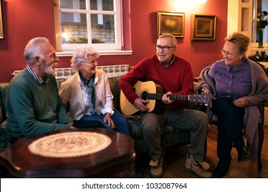 Old senior man playing guitar with his friends, making great party at nursing home