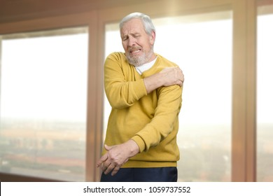 Old senior man with shoulder pain. Grandpa with shoulder inhury at home. Windows background.