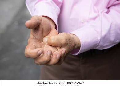 old senior man suffering from trigger finger, cps or carpal tunnel syndrome, gout disease, arthritis inflammation, hand pain; health care or body care concept