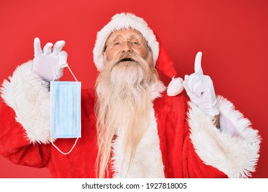 Old senior man wearing santa claus costume holding safety mask smiling with an idea or question pointing finger with happy face, number one