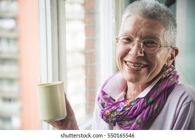 Old senior woman drinking a warm beverage, coffee or tea, looking through the window