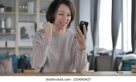 Old Senior Woman Excited for Success while Using Smartphone