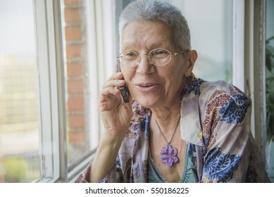 Old senior woman having a cheerful conversation over her mobile phone, talking with a friend or a relative