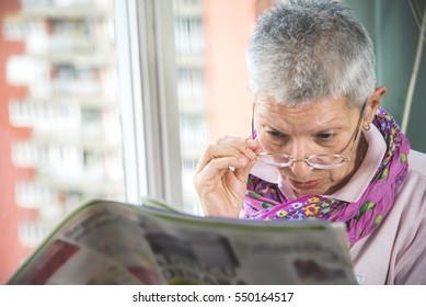 Old senior woman having troubles reading a magazine with her spectacles