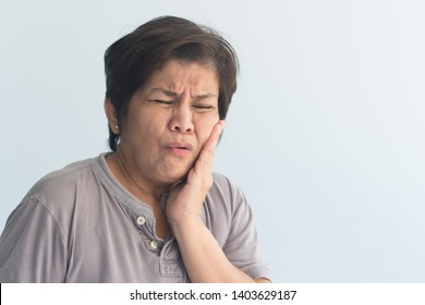 old senior woman suffering from toothache, tooth decay, tooth sensivity; oral health care concept