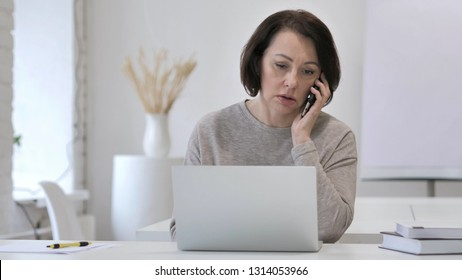 Old Senior Woman Talking on Phone and Working on Laptop