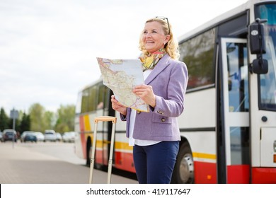 Old senior woman tourist holding a paper map in a bus station in Berlin, Germany, Europe
