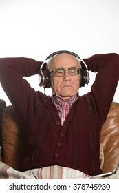 old seniour man wearing headphones and listening music wearing red sweater