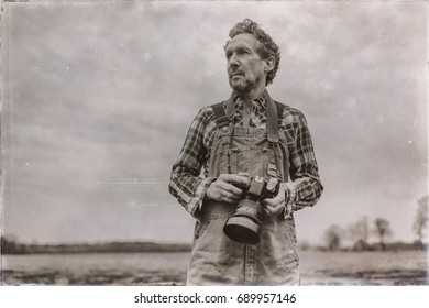 Old sepia photo of nature photographer standing outdoor in grassy area.