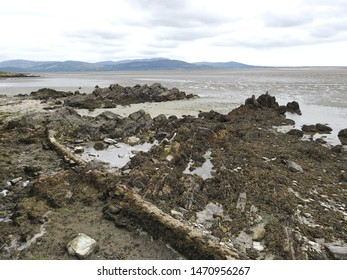 Old sewage waste pipe on Blackrock Beach, Dundalk, County Louth, Ireland, going through the rocks into the ocean, with the Cooley Mountains in the distant background.