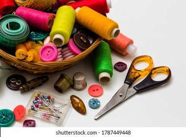 Old sewing accessories for sewing handmade on a white background, a spool of thread, scissors, buttons. A set for needlework. View from above