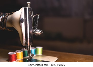 Old sewing machine with colour thread, on a old grungy work table. Tailor's work table. textile or fine cloth making. industrial fabric