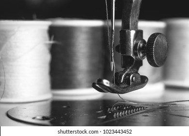 Old sewing machine with colour thread and needle, on a old grungy work table. Tailor's work table. textile or fine cloth making. industrial fabric black and white