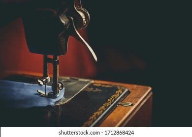 Old sewing machine, the man who sews on it, in dark colors
