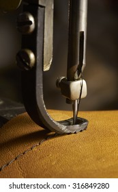 Old sewing machine needle and brown leather with seam
