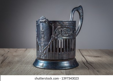 Old shabby heavily used Russian glass-holder made of forged steel with stamped pattern of plant and image of Kremlin tower with battlement on wood texture table lit with artificial light