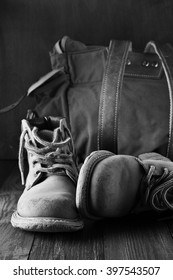 Old shabby leather hiking boots and backpack on wooden background. Monochrome black and white image.