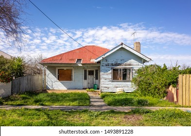 An old and shabby residential house with an unattended front yard. Australian weatherboard home with a corrugated iron roof.