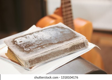 old shabby tattered book on yellow guitar background, author's song preparation