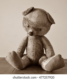 Old shabby teddy bear sitting on a wooden surface