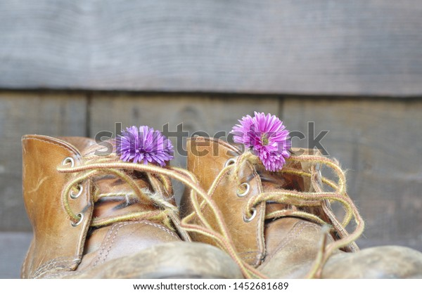 Old shabby walking boots with blossoms