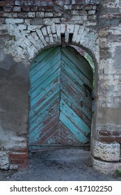Old shabby wooden turquoise door in ancient brick arch