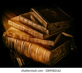 Old Shakespeare books stack on dark wooden surface in warm directional light. Filter effects.