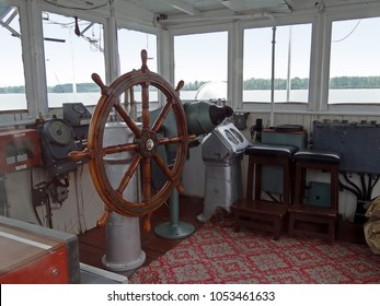 Old ship bridge interior with ship's wheel, rudder and navigation tools