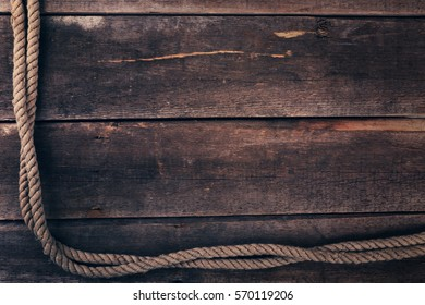 old ship rope on wooden plank background