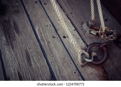 Old ship teak deck weathered and grunge with iron ring, chain and rope, wooden texture and background