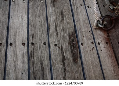 Old ship teak deck weathered and grunge with iron ring and rope, wooden texture and background