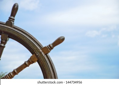 old ship wheel with blue sky background