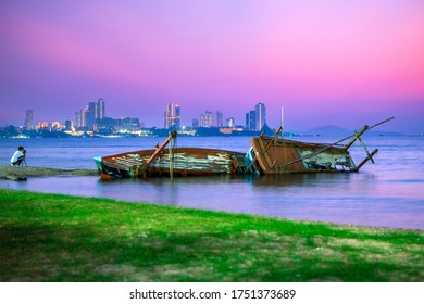 The old shipwreck was abandoned, standing on the beach. Shipwrecks at Kratinglay beach, ChonBuri, Thailand There is Pattaya city in the background.