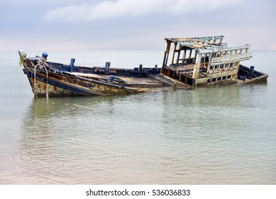 An old shipwreck  , Wrecked boat abandoned stand on beach or Shipwrecked off the coast of Thailand.
