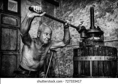 Old shirtless winemaker farmer working on a traditional wine press. Black and white picture